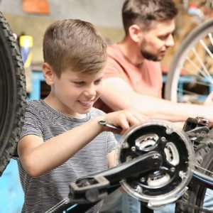boy and man working on their bikes hobby workshop